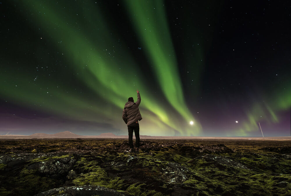 young boy hunting for the northern lights in Iceland